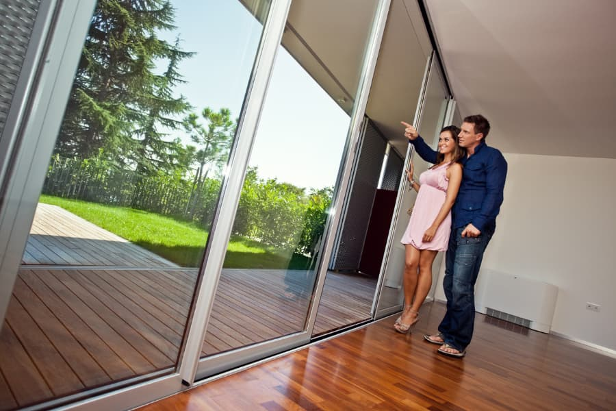 Young Couple Admires Large Sliding Glass Door